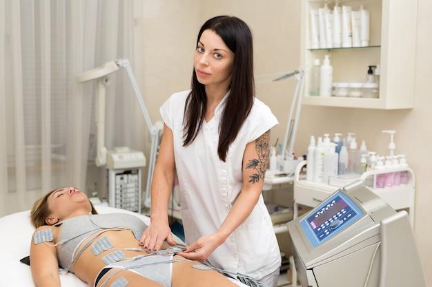 Профессиональный косметолог делает антицеллюлитный массаж молодой женщине с помощью биостимулирующего аппарата. женщина в салоне красоты медицинского спа-центра антицеллюлитная электростимуляционная терапия