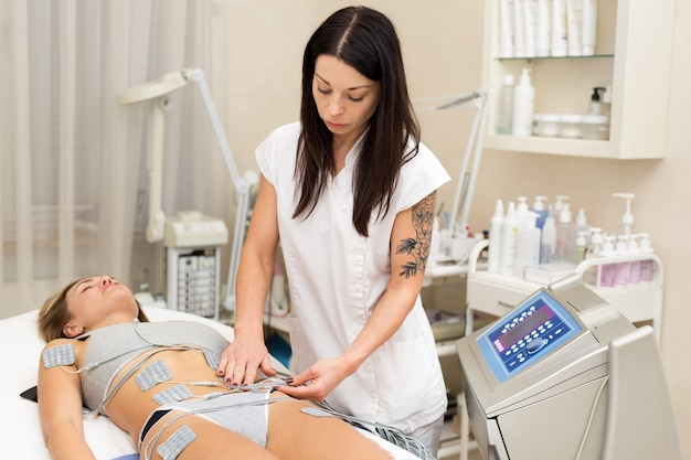 Профессиональный косметолог делает молодой женщине антицеллюлитный массаж.