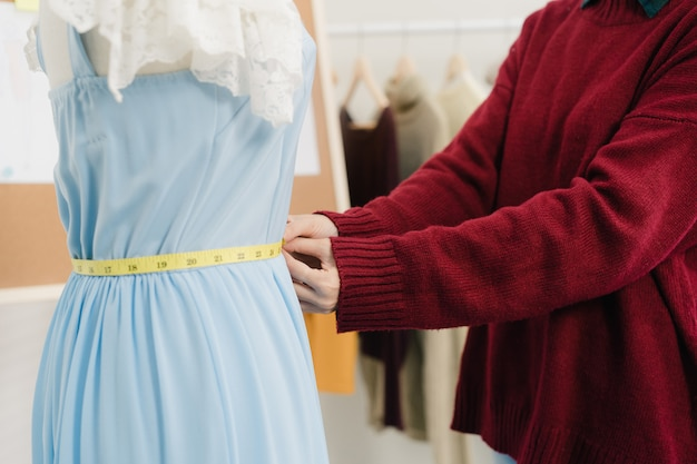 Professional beautiful asian female fashion designer working measuring dress on a mannequin clothing