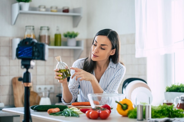 プロの美しい幸せな若い女性は、彼女の家のキッチンでの健康的な生活と三脚のカメラを見ていることについて彼女のキッチンチャンネルのためにブログを書いています
