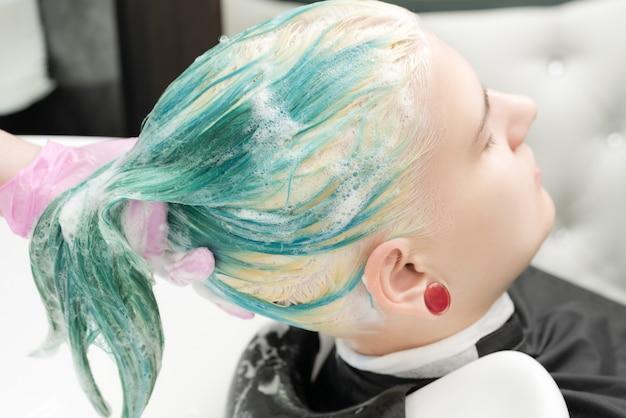 Профессиональный парикмахер салона красоты, мытье зеленых волос молодой женщины шампунем в раковине ч ...