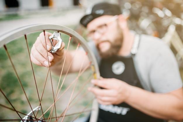 エプロンのプロの自転車マスターは、サービスツールのクローズアップで自転車のスポークと修理ホイールを調整します。