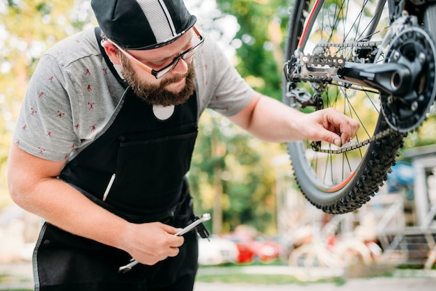 Professional bicycle mechanic in apron adjusts bike chain. cycle workshop outdoor. bicycling sport, bearded service man work with wheel