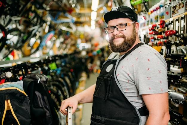 자전거 가게에서 바퀴를 가진 전문 자전거 정비공. 사이클링 스포츠 매장.