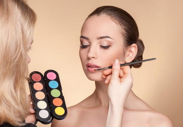 Профессиональный светловолосый визажист наносит помаду на женские губы