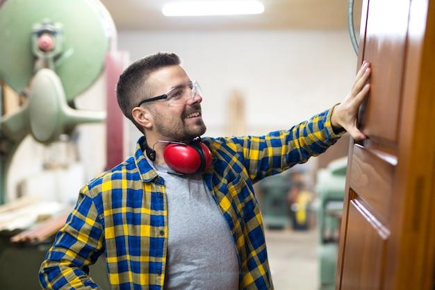 Профессиональный светловолосый плотник средних лет проверяет качество деревянных изделий в своей столярной мастерской