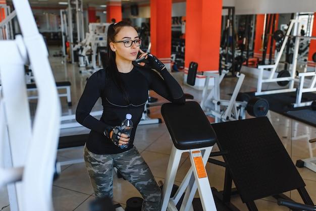 Профессиональный спортсмен бодибилдинга расслабиться после изнурительной тренировки. спортсмен расслабляется и пьет воду из спортивной бутылки в интерьере тренажерного зала.