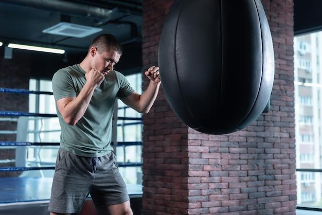 Professional boxer feeling motivated while training hard standing near big black punching bag