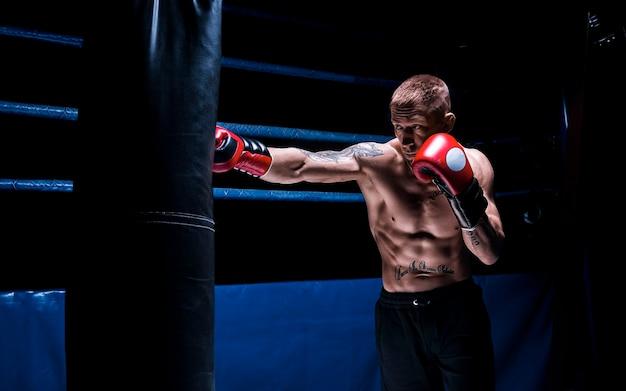 Профессиональный боксер бьет по сумке на фоне ринга. вид сбоку. понятие о спорте и классическом боксе. смешанная техника