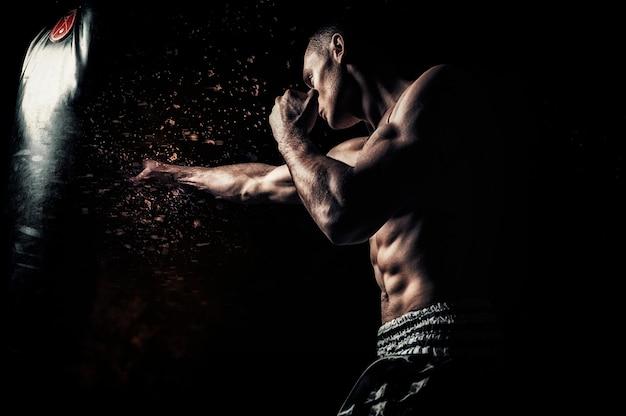 プロボクサーが鞄にぶつかる。スポーツ、ボクシング、健康的なライフスタイル、mmaの概念。ミクストメディア