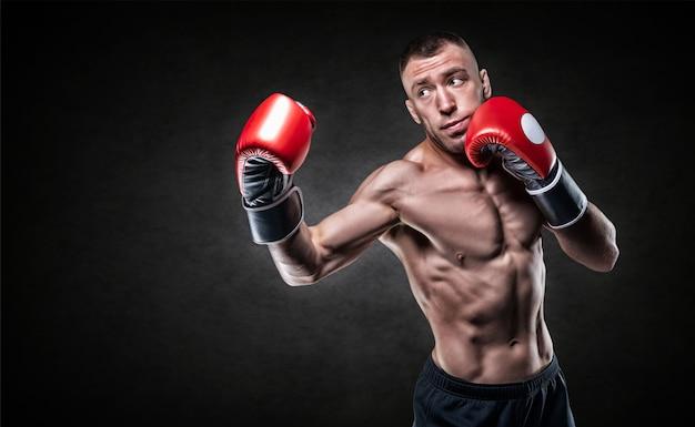 Профессиональный боксер в красных перчатках тренирует удары. концепция бокса. смешанная техника
