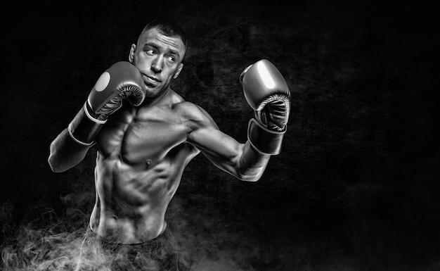 Профессиональный боксер практикует удары в дыму. концепция ставок на спорт. смешанная техника