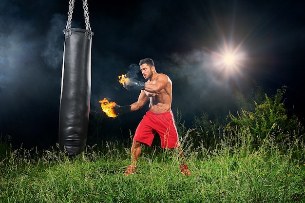 Professional boxer punching sandbag in the field at night
