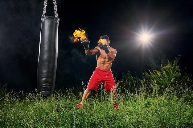 Professional boxer punching sandbag with burning gloves