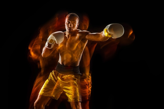 Professional boxer training isolated on black studio background in mixed light
