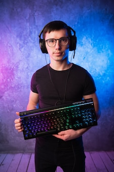 Professional boy gamer holding gaming keyboard over colorful pink and blue neon lit wall.