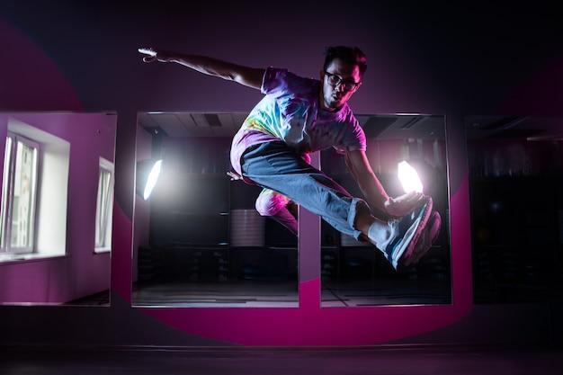 핑크 네온 불빛에서 현대 힙합 댄스를 연습하는 전문 브레이크 댄서