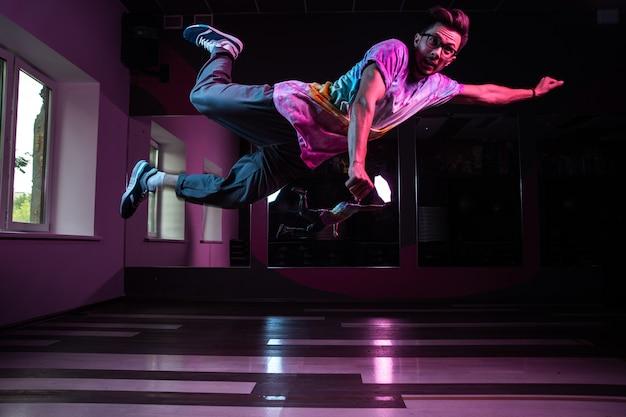 Профессиональный танцор брейк-данса в движении, практикует современный хип-хоп танец в розовом неоновом свете