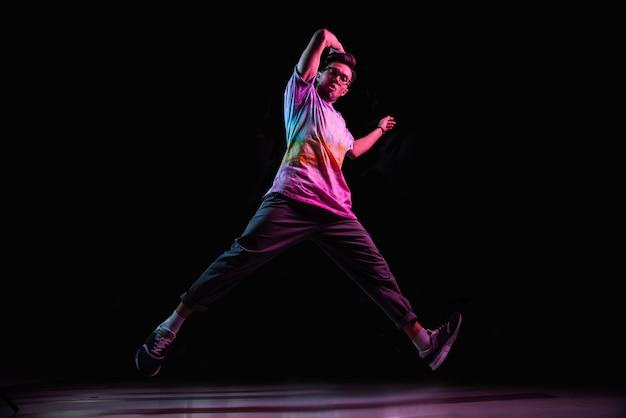 Профессиональный танцор брейк-данса прыгает, практикует современный хип-хоп танец в розовом неоновом свете