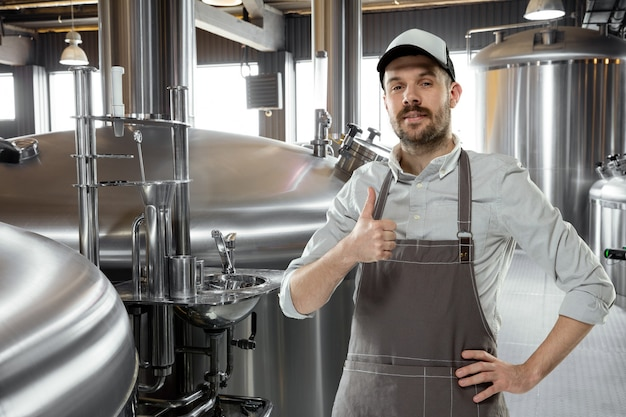 Professional brewer on his own craft alcohol production. specialist, man wearing in workwear posing confident with thumb up. concept of open business, eco product, craft brewery, individual factory.