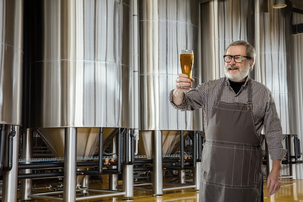 Professional brewer on his own craft alcohol production. Premium Photo