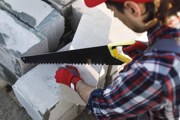 전문 벽돌공이 오토 클레이브 콘크리트 블록을 절단하고 있습니다.