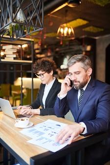 Профессиональный брокер консультирует клиентов по телефону при работе с финансовыми бумагами за чашкой чая в кафе