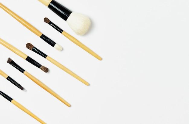 Профессиональные коричневые деревянные кисти для макияжа лежат по диагонали слева. кисть для макияжа, изолированные на белом фоне. горизонтальный шаблон для визитной карточки визажиста или дизайна флаера.