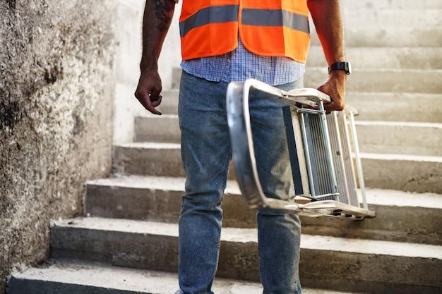 금속 사다리를 들고 전문 건축업자를 닫습니다.
