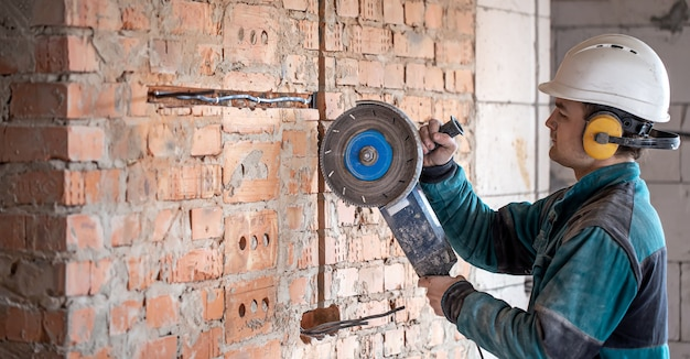 A professional builder in work clothes works with a cutting tool.