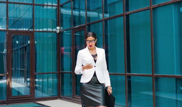 Professional business afro woman in elegant white jacket and skirt with folder with documents in her hands  use smartphone