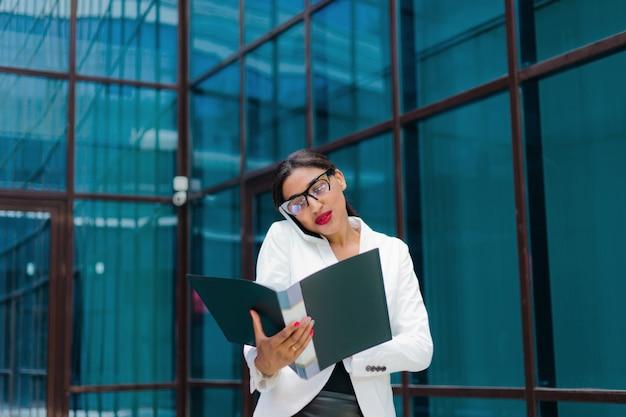 Профессиональная деловая афро женщина в элегантной белой куртке и юбке с папкой с документами в руках