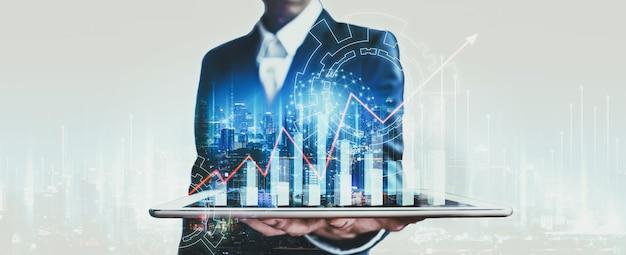 ネットワーク都市でタブレットを使用し、タイのバンコクで夜にデジタル マーケティング チャート グラフィックを使用するプロのビジネスマン