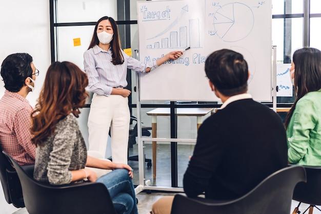 保護マスクを着用したコロナウイルスの検疫での専門的なビジネスプレゼンテーション会議