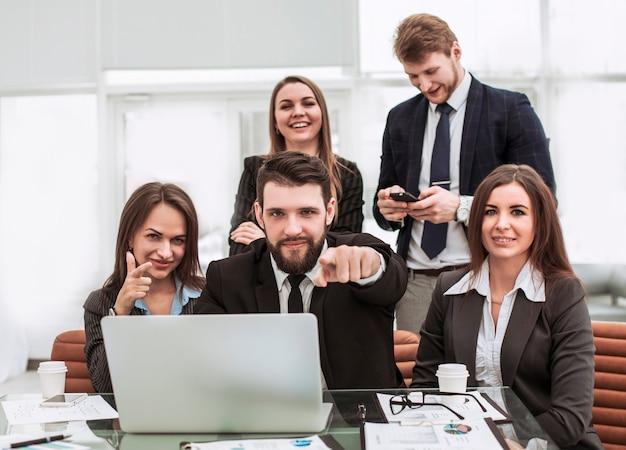 바탕 화면 근처의 전문 비즈니스 팀이 함께 집게 손가락을 앞으로 보여줍니다.