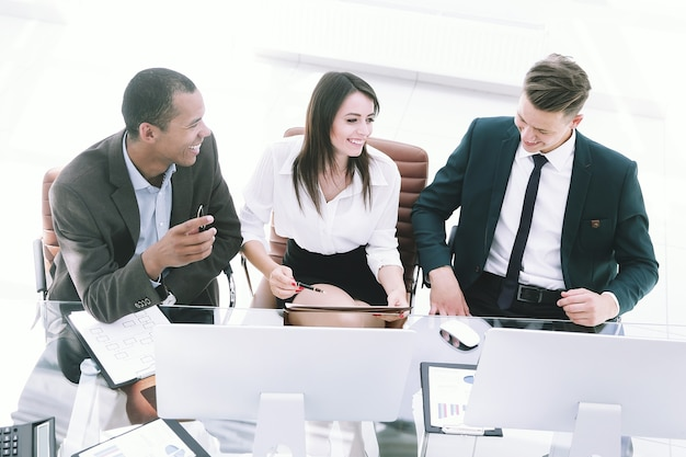 Профессиональная бизнес-команда, сидя за столом в офисе