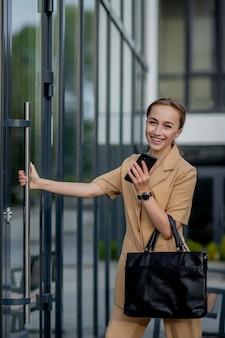 야외에서 휴대 전화를 사용 하여 전문 비즈니스 여자입니다. 도시에서 야외 산책하는 동안 스마트 폰에 여성 문자 메시지.