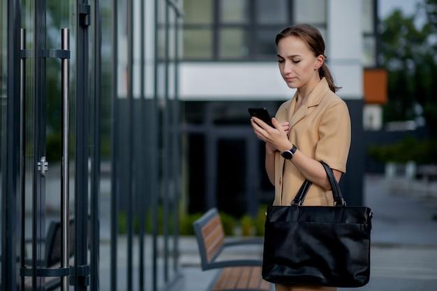 야외에서 휴대 전화를 사용하는 전문 비즈니스 여성. 도시에서 야외를 걷는 동안 스마트 폰으로 여성 문자 메시지.