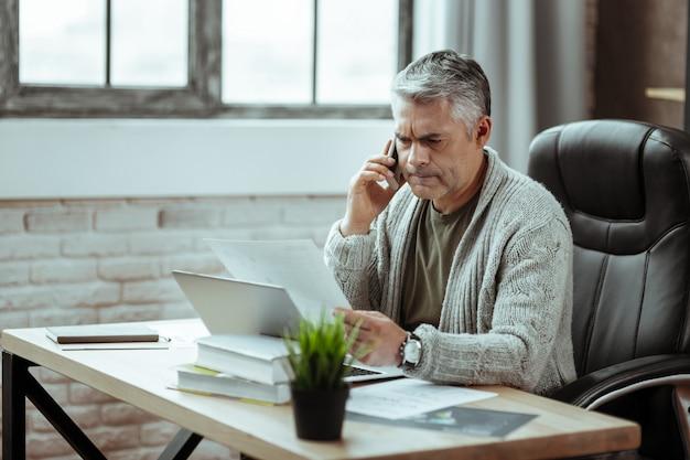 プロのビジネスマン。電話で話している間彼の仕事について考えている素敵な真面目な男