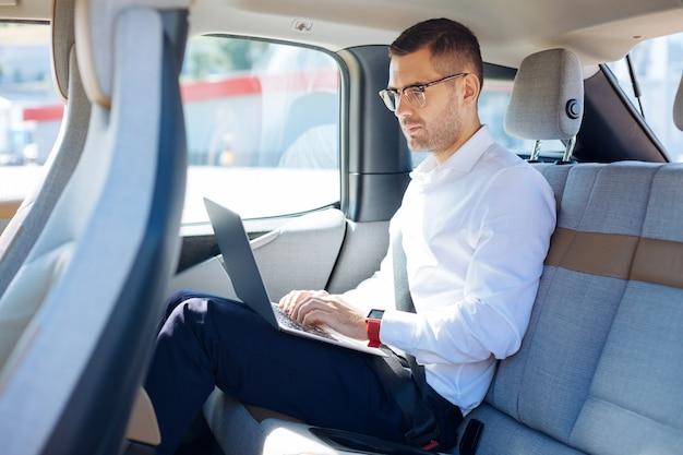 プロのビジネスマン。車から作業しながら彼のラップトップを使用してスマートな成功した実業家