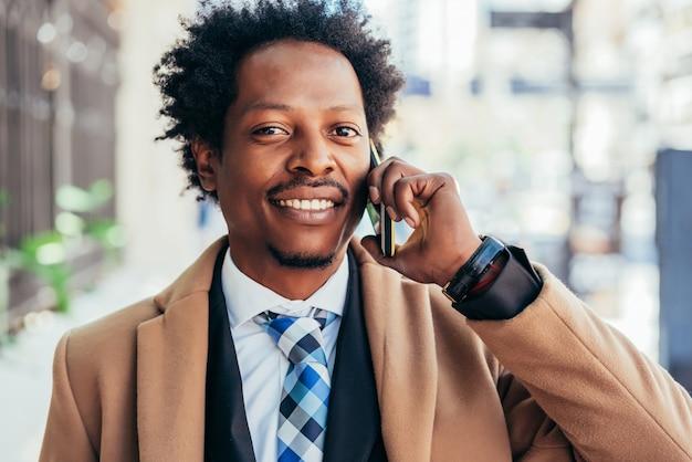 Профессиональный бизнесмен разговаривает по телефону во время прогулки по улице