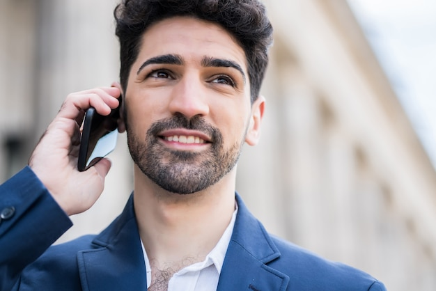 거리에 야외에서 걷는 동안 전화 통화하는 전문 사업가.