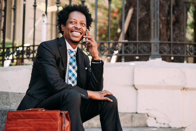 Professional businessman talking on the phone while sitting on stairs outdoors. business and technology concept.
