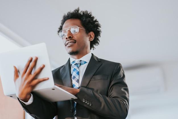 현대 사무실에서 작업하는 동안 자신의 노트북을 사용하는 전문 사업가. 비즈니스 및 기술 개념.