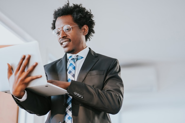 現代のオフィスで働いている間彼のラップトップを使用してプロのビジネスマン。ビジネスと技術の概念。