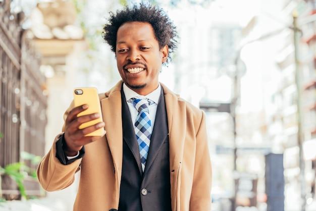 거리에 야외에서 서있는 동안 자신의 휴대 전화를 사용하는 전문 사업가