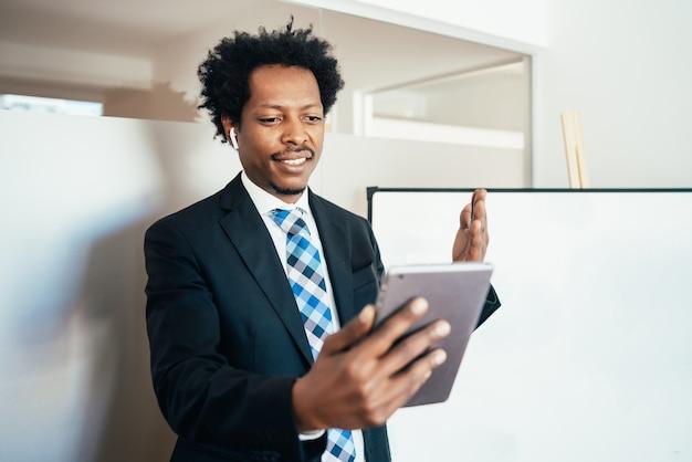 Uomo d'affari professionista in una riunione virtuale in videochiamata con tablet digitale in ufficio. concetto di affari.