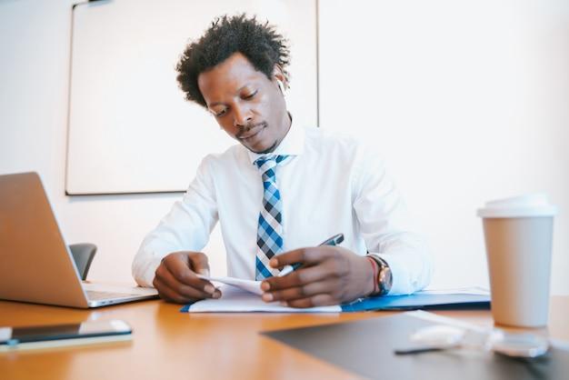 Uomo d'affari professionista che lavora nel suo ufficio moderno. concetto di affari e successo.