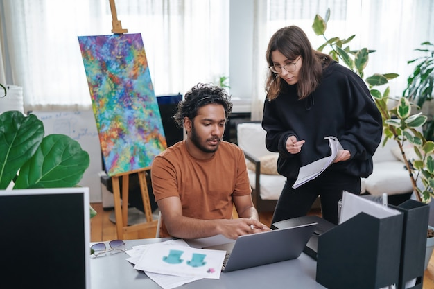 プロのビジネスマンが一緒に仕事をし、現代のオフィスのテーブルで計画を立てます。白人とインドのデザイナーとそのプロジェクト。