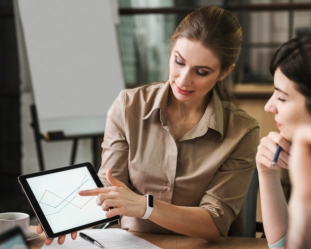 屋内での会議中にタブレットを使用するプロのビジネスマン
